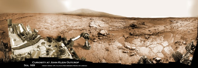 Curiosity accomplished historic 1st drilling into Martian rock on Feb 8, 2013 shown in this panoramic photo mosaic view of Yellowknife Bay where the robot is currently working. Robotic arm is pressing down on outcrop of veined hy-drated minerals – dramatically back dropped with her ultimate destination; Mount Sharp. Credit: NASA/JPL-Caltech/Ken Kremer/Marco Di Lorenzo